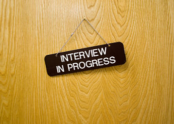 Door with interview sign hanging from it.
